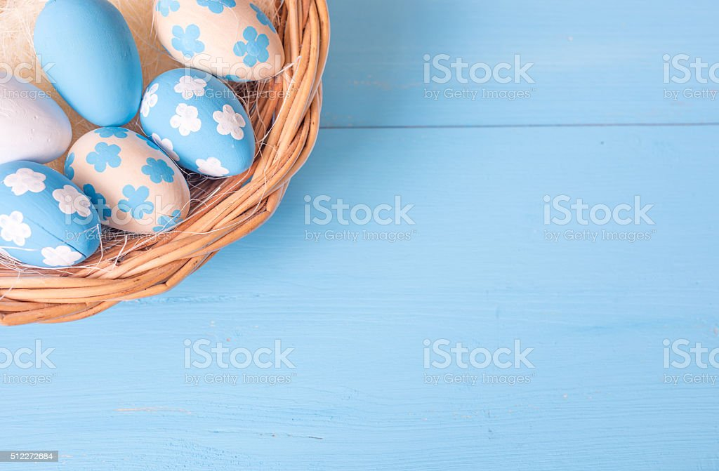 Easter eggs in wicker basket on blue wooden background stock photo