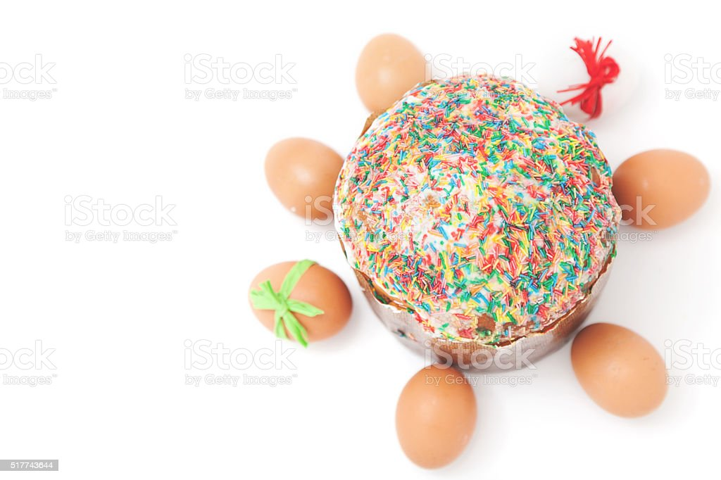 Easter eggs lie around cake on white background stock photo