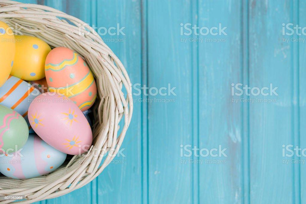 Easter eggs on blue wood in basket. Seasonal background. stock photo
