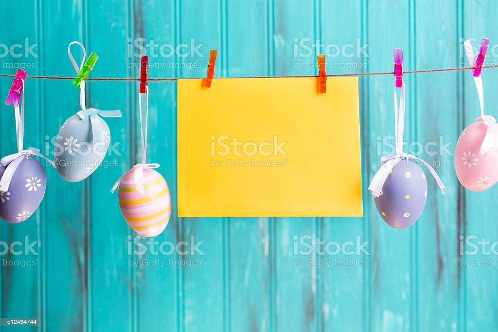 Easter eggs ornaments hang on blue wood. Seasonal. Blank sign. stock photo