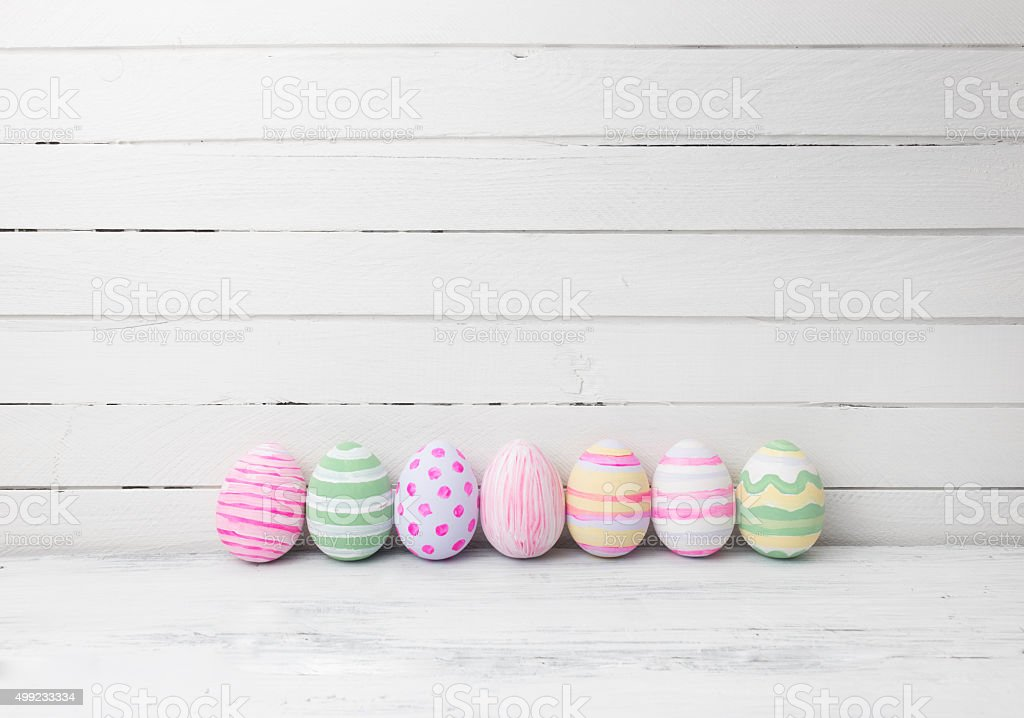 Easter eggs painted in pastel colors on white wooden background. stock photo