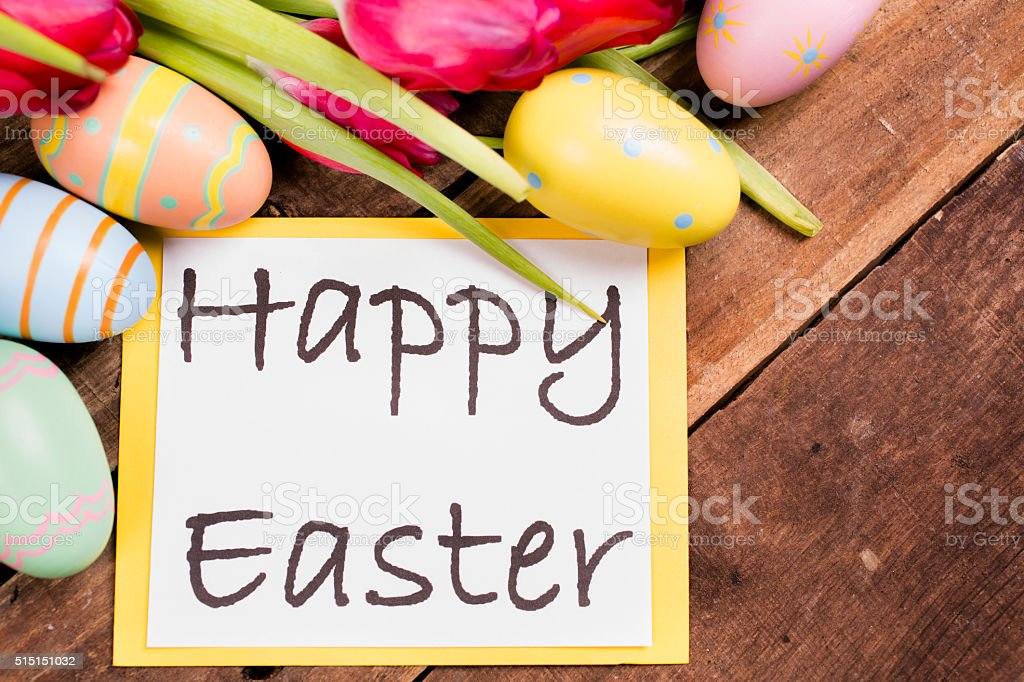 Easter eggs, tulips on vintage wood background. Happy Easter sign. stock photo