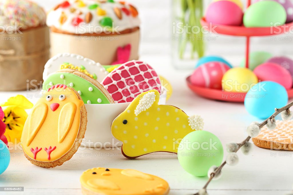 Easter eggs with cookies on a white wooden table stock photo