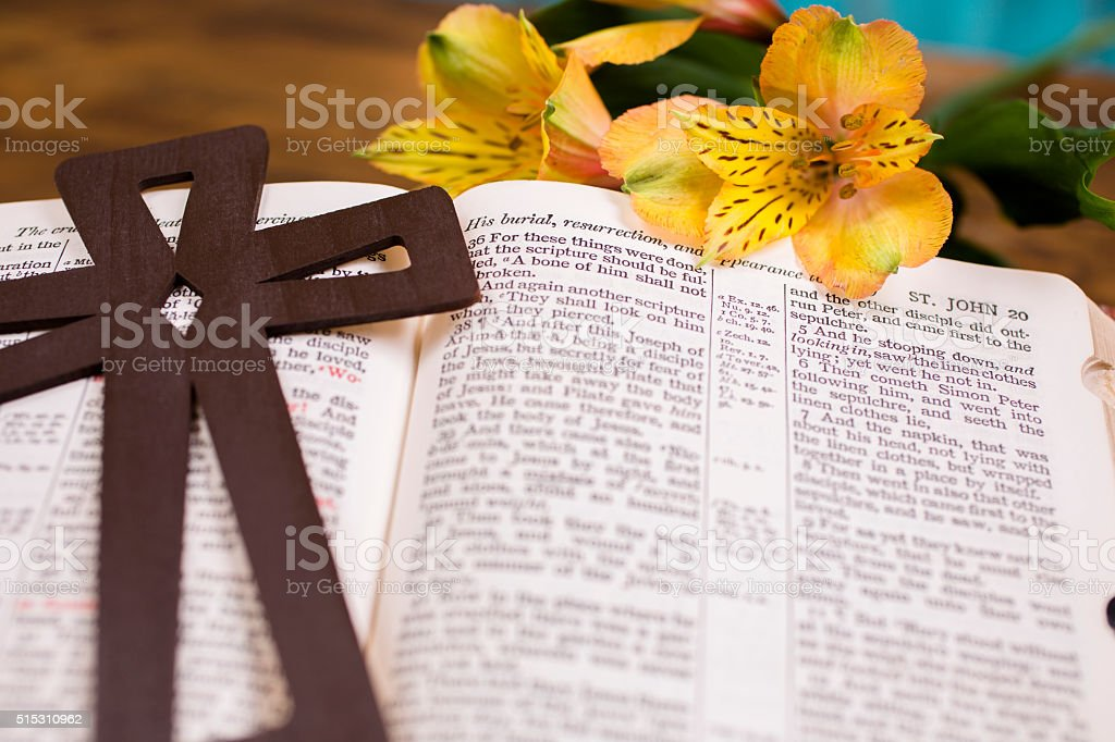 Easter.  Flowers and cross on open Christian Bible. stock photo