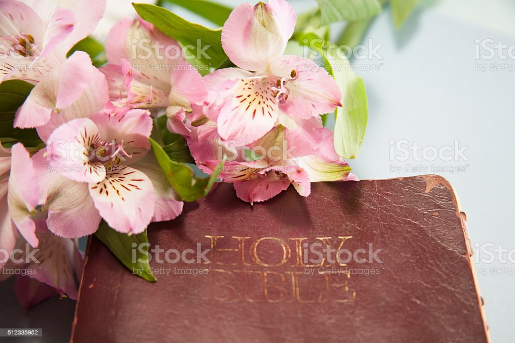 Easter. Flowers on closed Christian Bible. stock photo