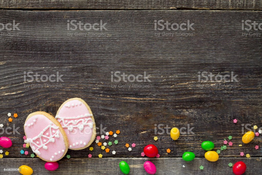 Easter frame. Cookies Easter eggs and sugar confectionery sprinkling on a wooden table. Easter recipe. Copy space. stock photo