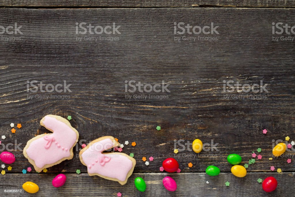 Easter frame. Easter Bunny Cookies and confectionery sugar sprinkling on a wooden table. Easter recipe. Copy space. stock photo