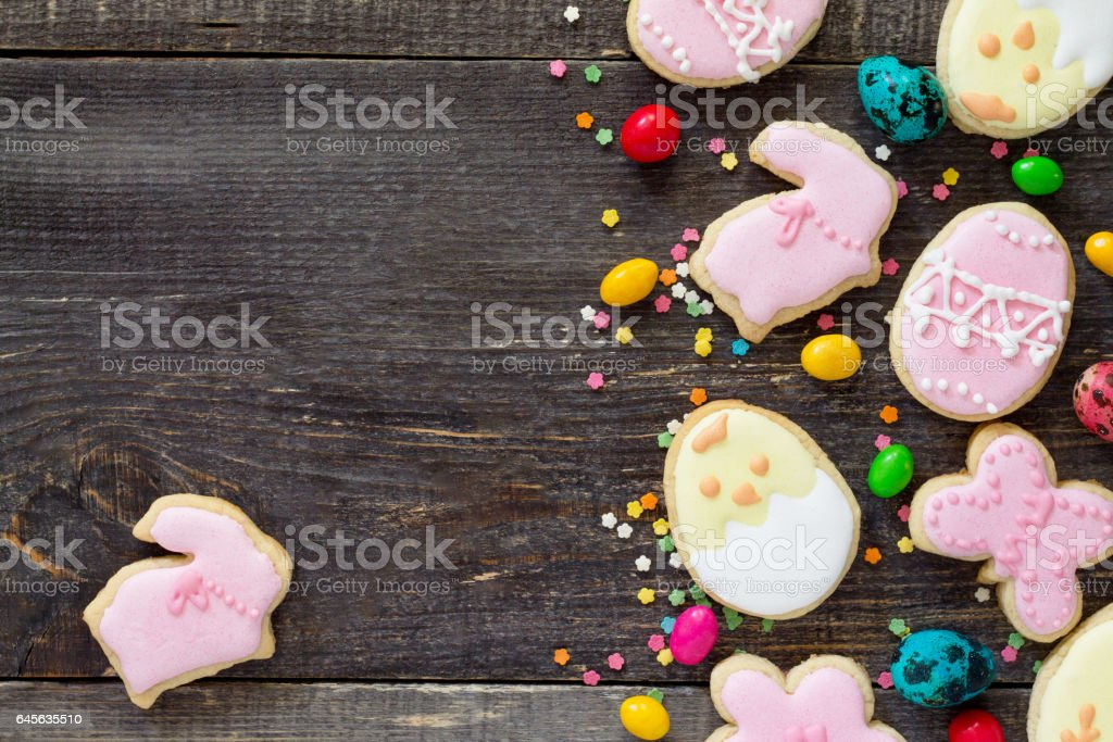 Easter frame. Easter eggs, various cookies and confectionery sugar sprinkling on a wooden table. Copy space, top view. stock photo
