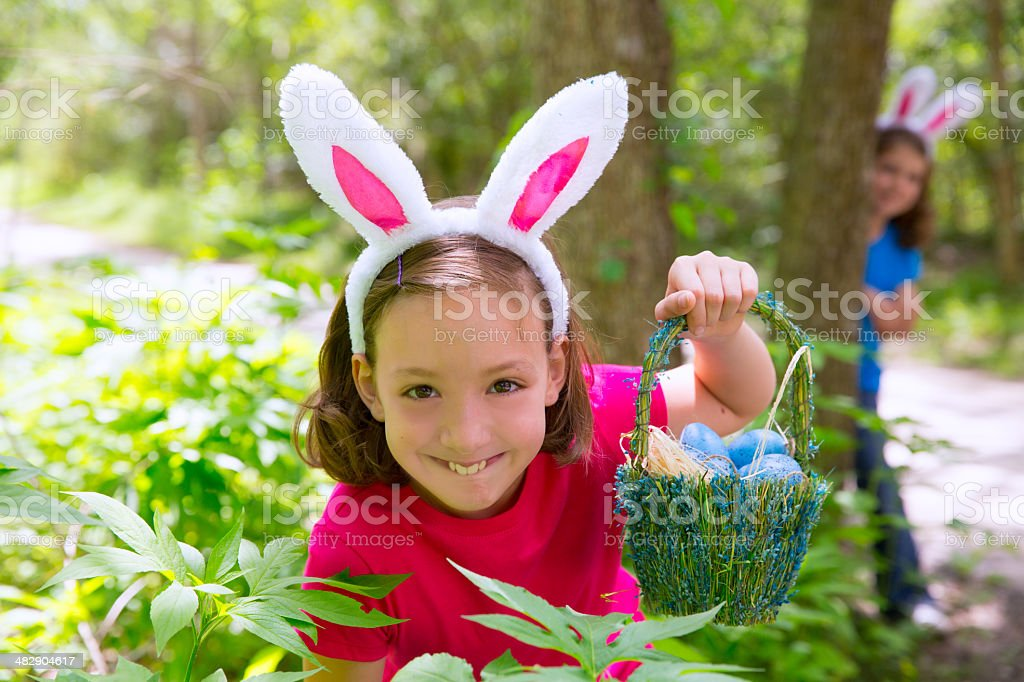 Easter girl with eggs basket and funny bunny face stock photo