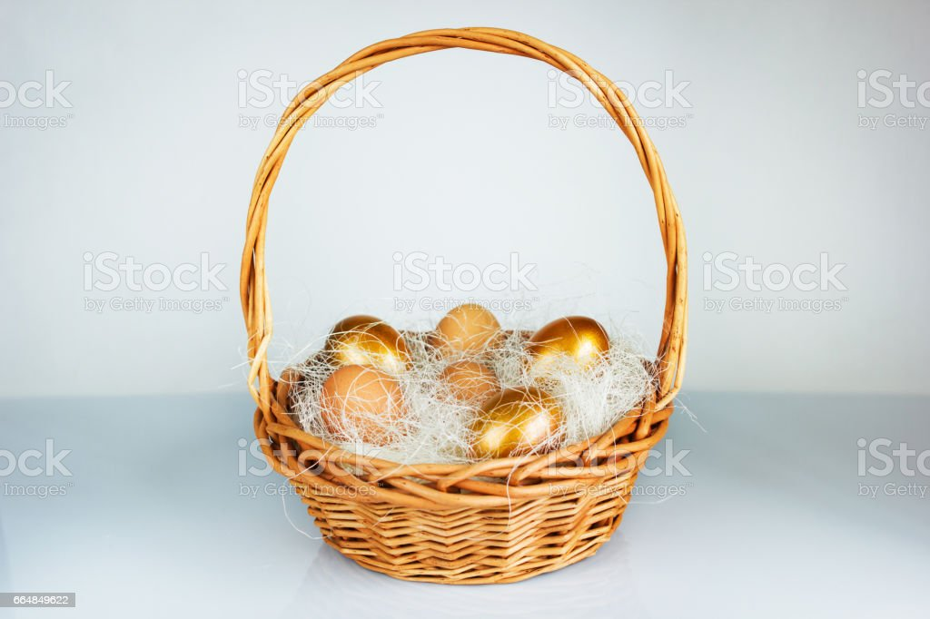 Easter golden eggs in a basket on table stock photo