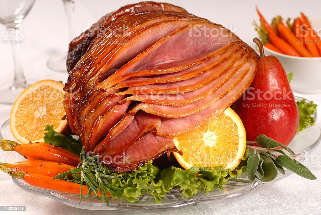 Easter ham with carrots, herbs and fruit stock photo