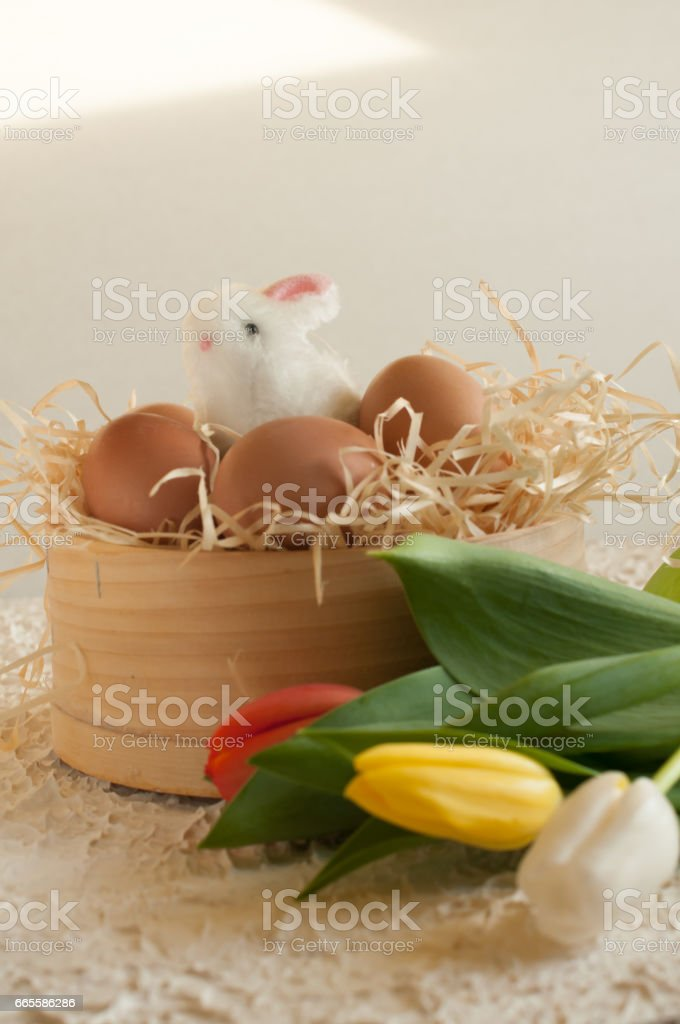 Easter holiday basket with eggs, flowers and easter bunny on rustic wooden stock photo