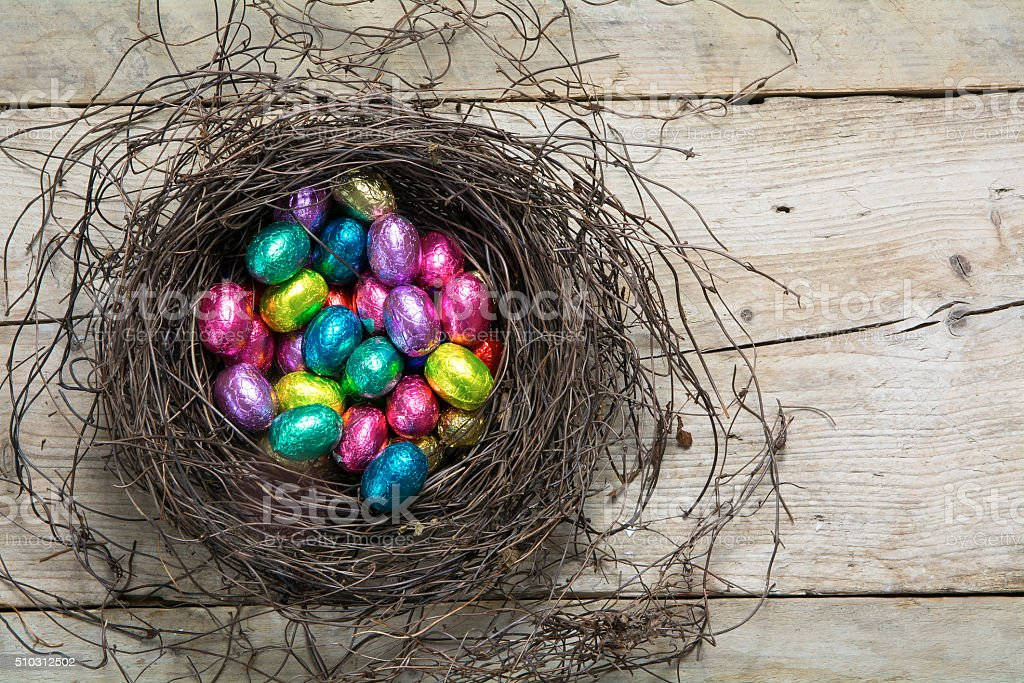 easter nest with wrapped chocolate eggs in pastel colors stock photo
