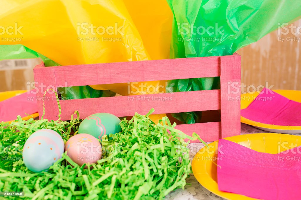 Easter party. Gift, eggs, plates, basket on table. stock photo