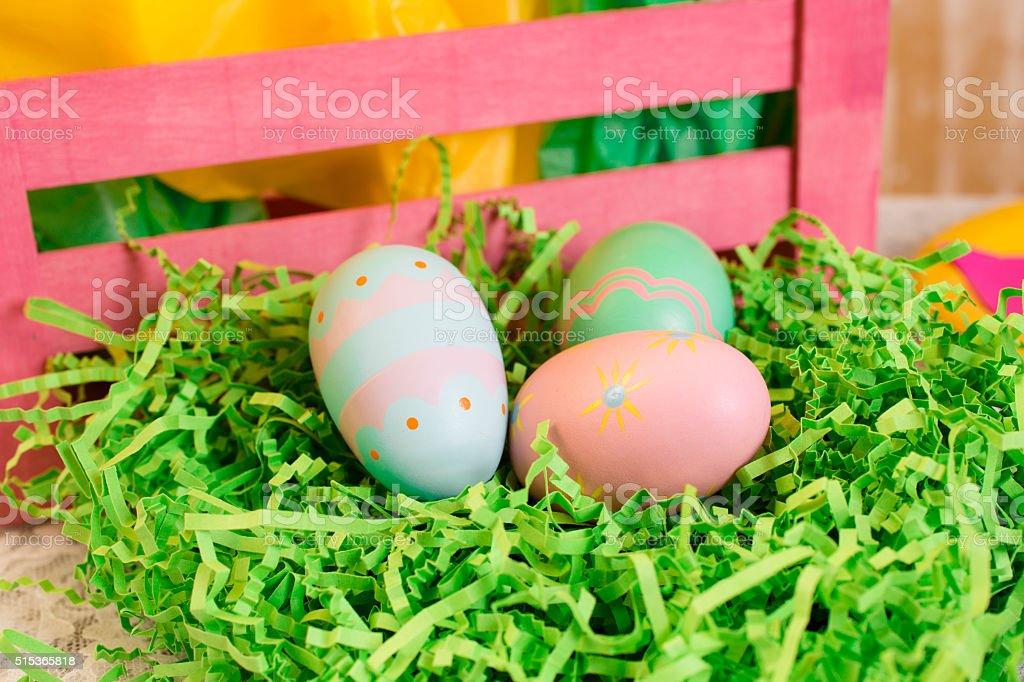 Easter party. Gift, eggs, plates, tulilps, basket on table. stock photo