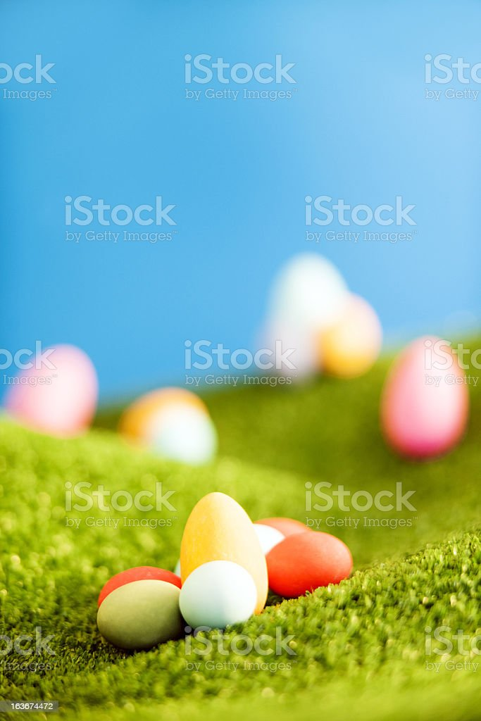 Easter sweets on grass hills with blurred background. royalty-free stock photo