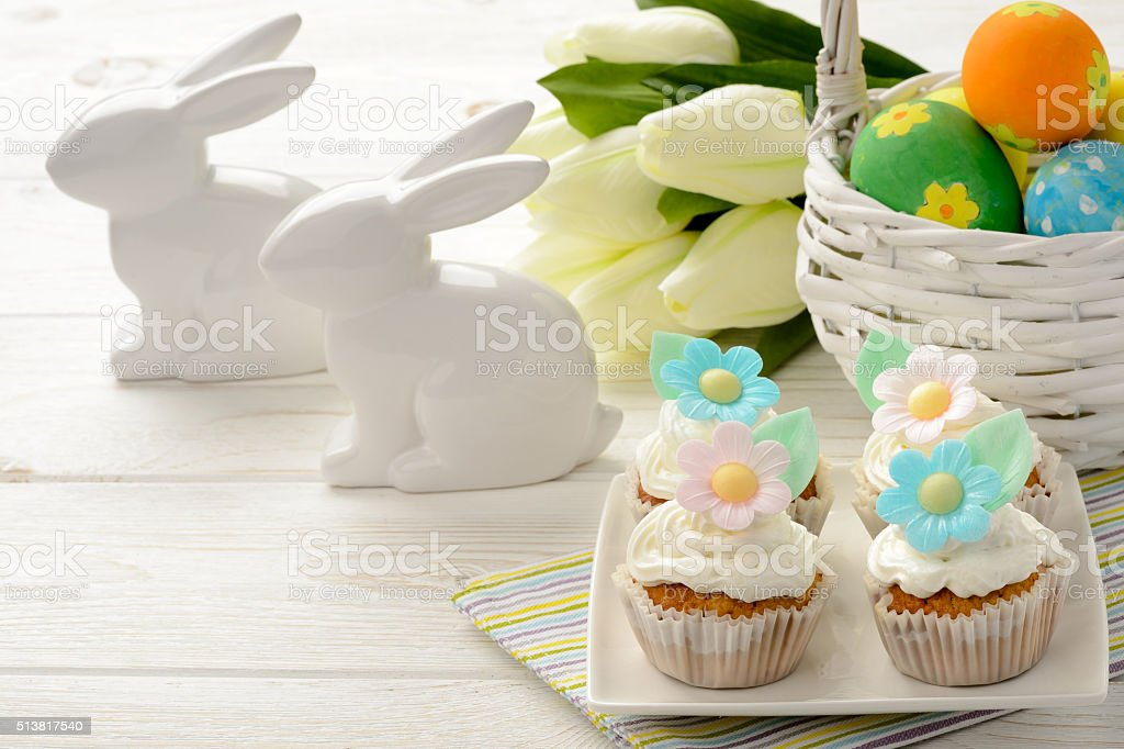 Easter table - basket with eggs, muffins and bunnies. stock photo