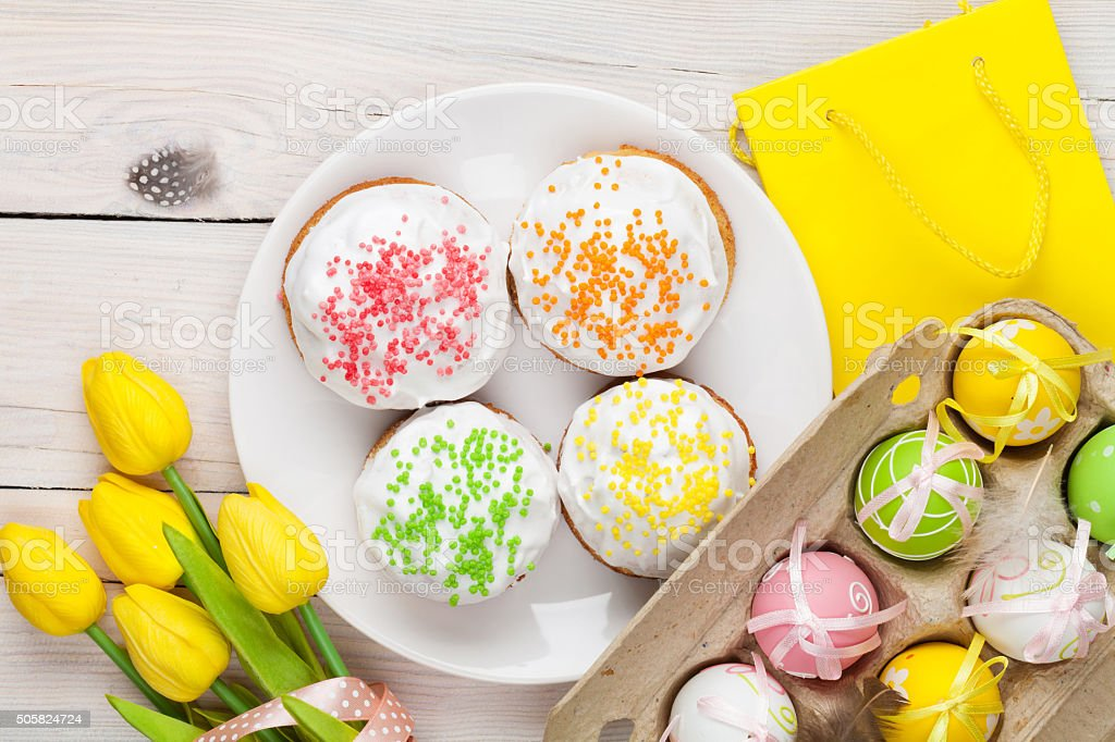 Easter with yellow tulips, colorful eggs and traditional cakes stock photo