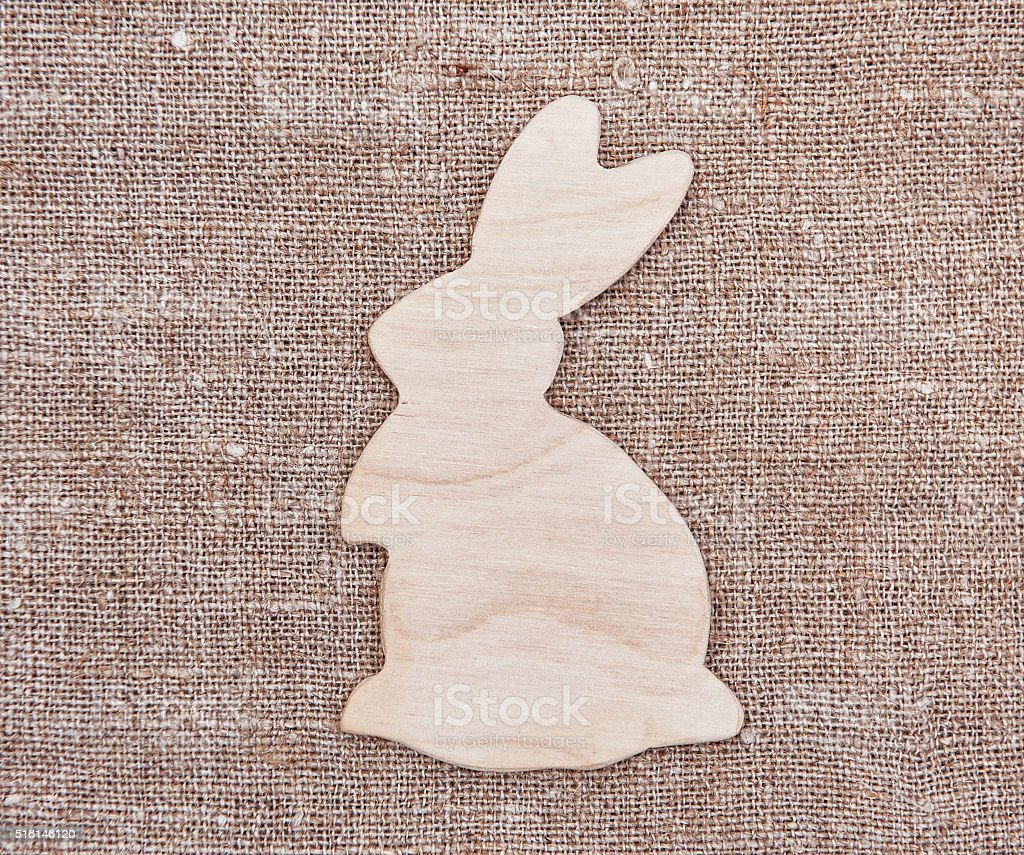 Easter wooden rabbit on the old burlap background stock photo