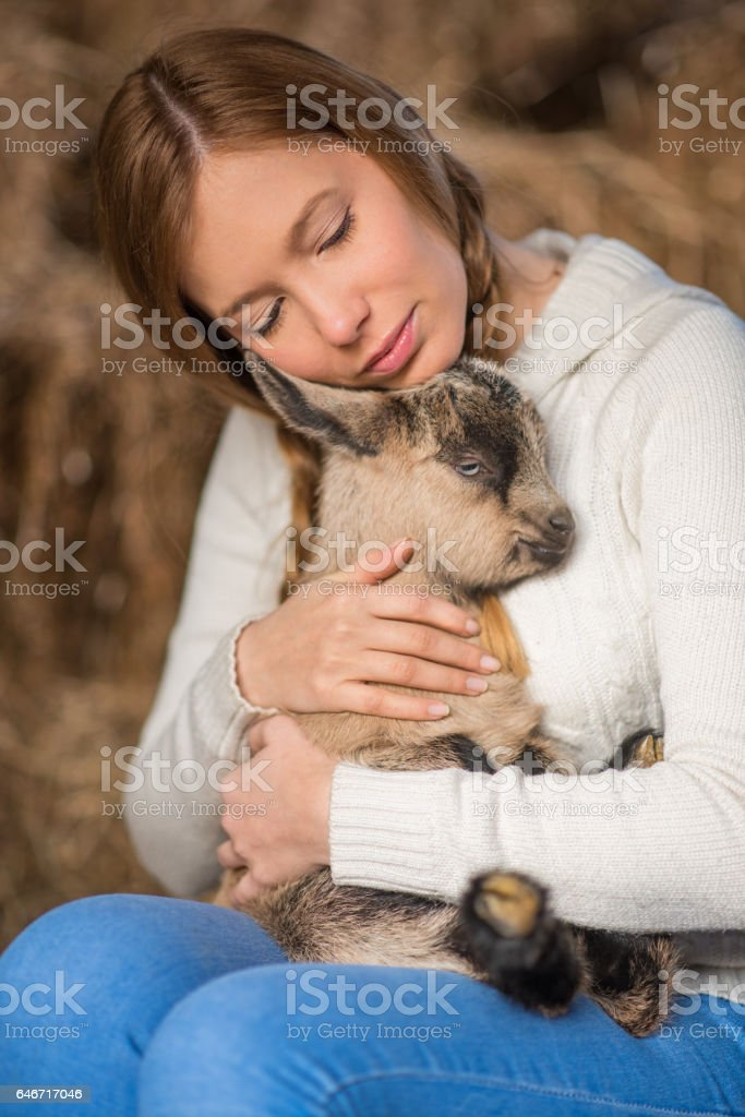 Eastern Europe: Lifestyle-Young woman hugging kid goat stock photo