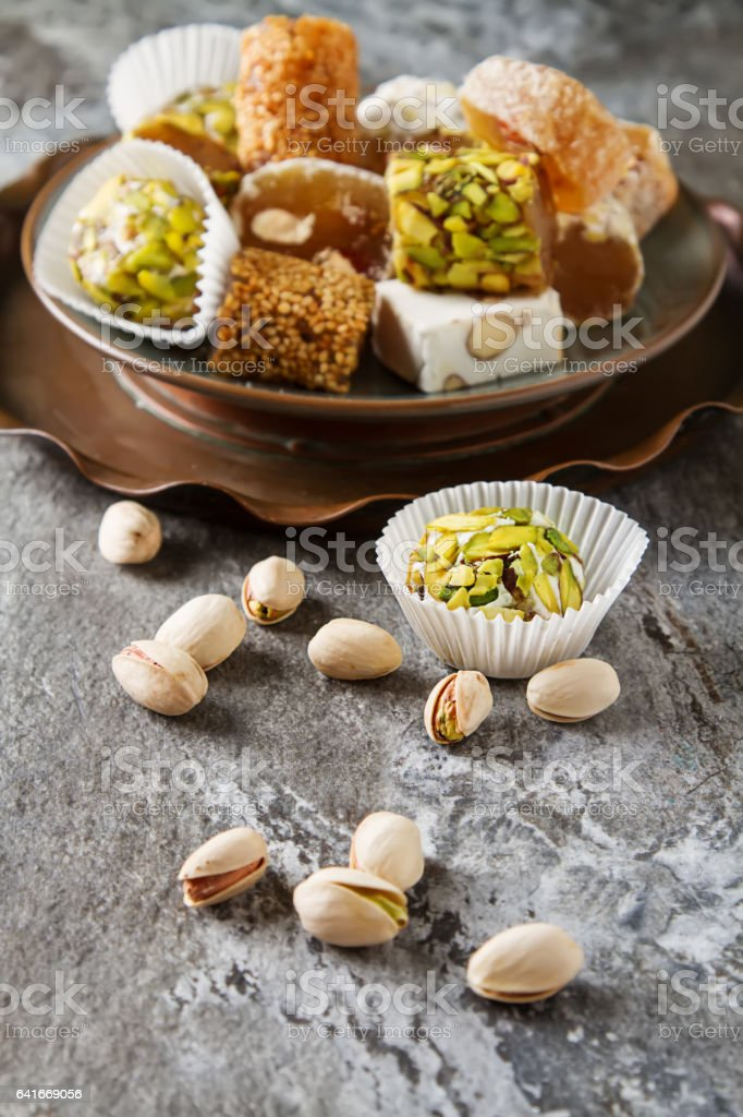 Eastern sweets. Turkish delight with pistachios in a vase. Dark gray stone background. stock photo