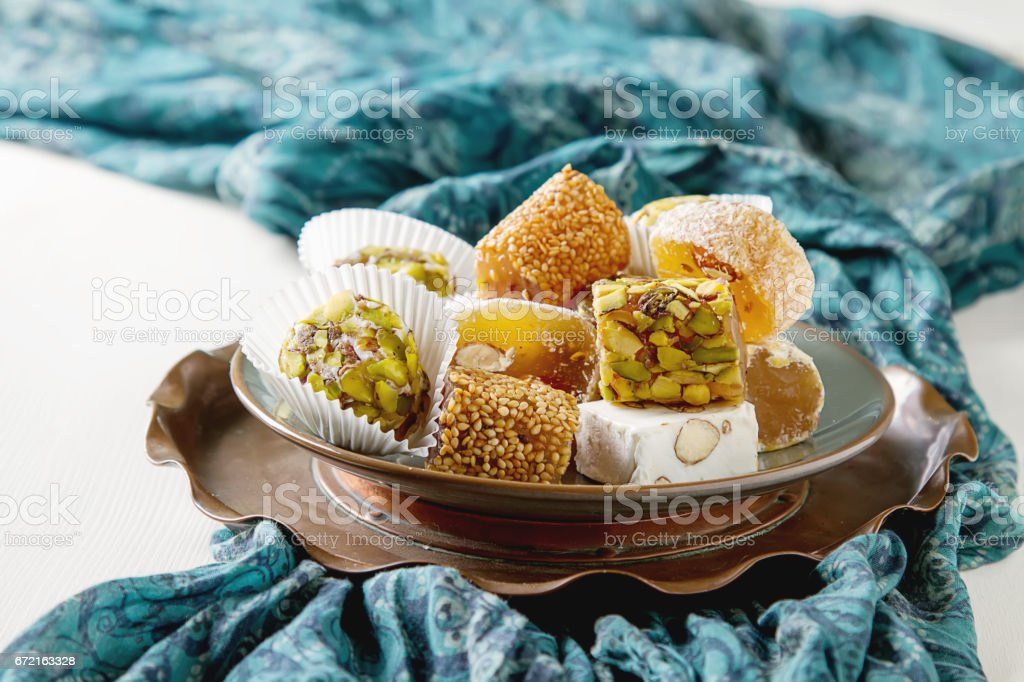 Eastern sweets. Turkish delight with pistachios in a vase. The fabric on  white background stock photo