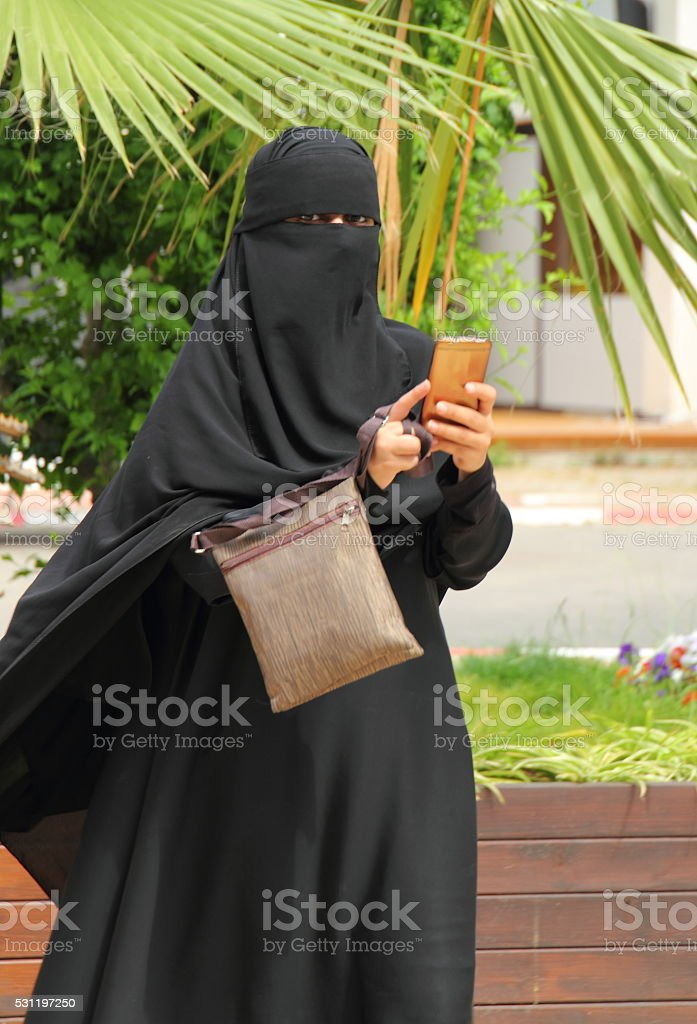 Eastern woman wearing a black Niqab and holding smartphone stock photo