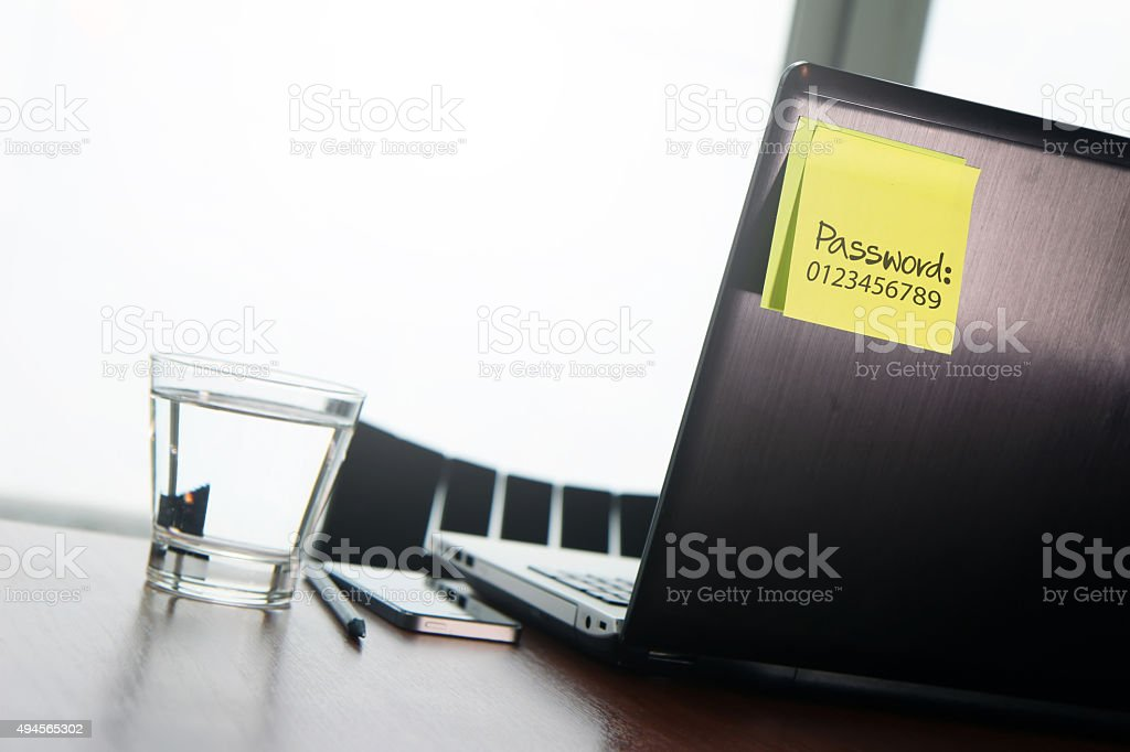easy password on sticky note on back Laptop stock photo
