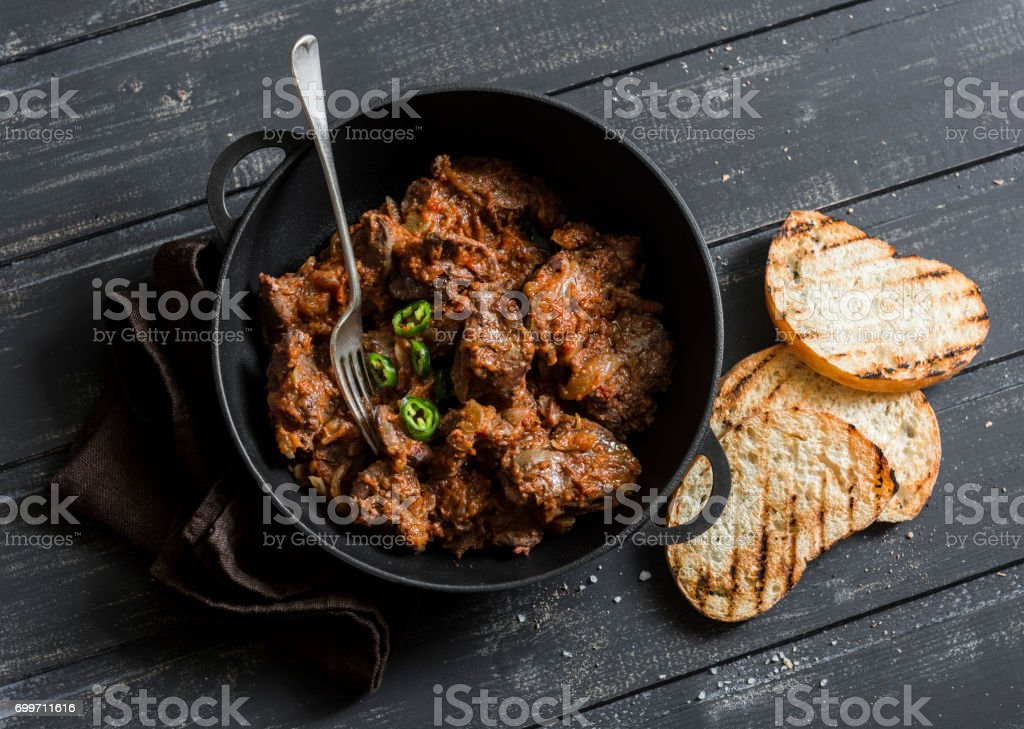 Easy peri-peri chicken livers in a cast iron skillet on a dark background, top view. Simple rustic lunch stock photo