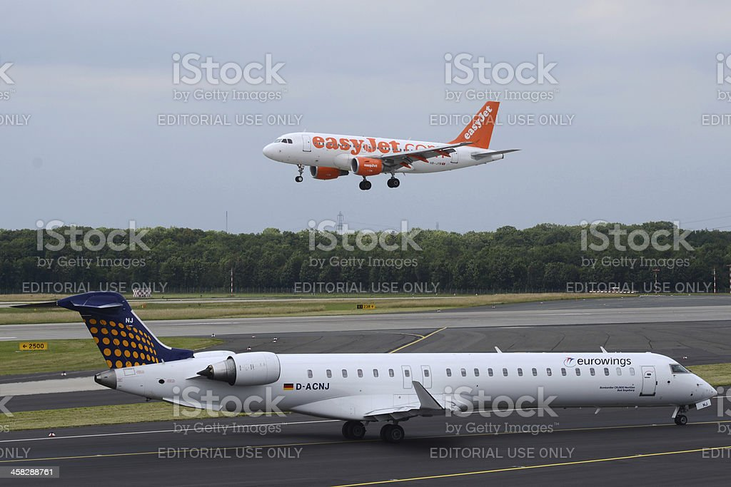 easyJet landing and eurowings taxiing for takeoff stock photo