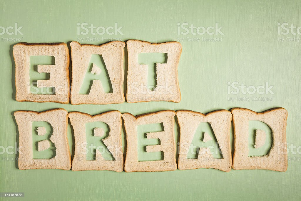 Eat bread text carved out of white loaf slices royalty-free stock photo