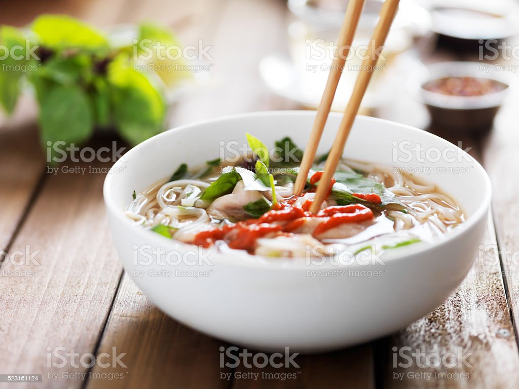 eating a bowl of vietnamese beef pho with chopsticks stock photo