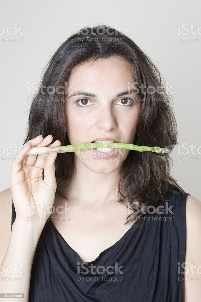 eating a green asparagus royalty-free stock photo