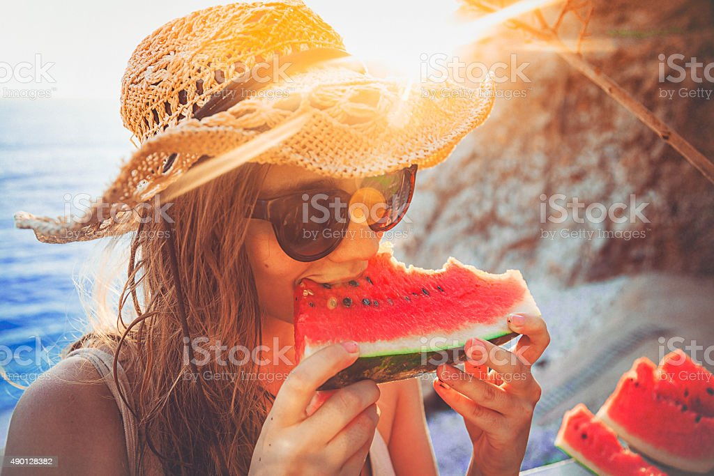 young woman having fun and eating juicy fresh watermelon outdoor at...