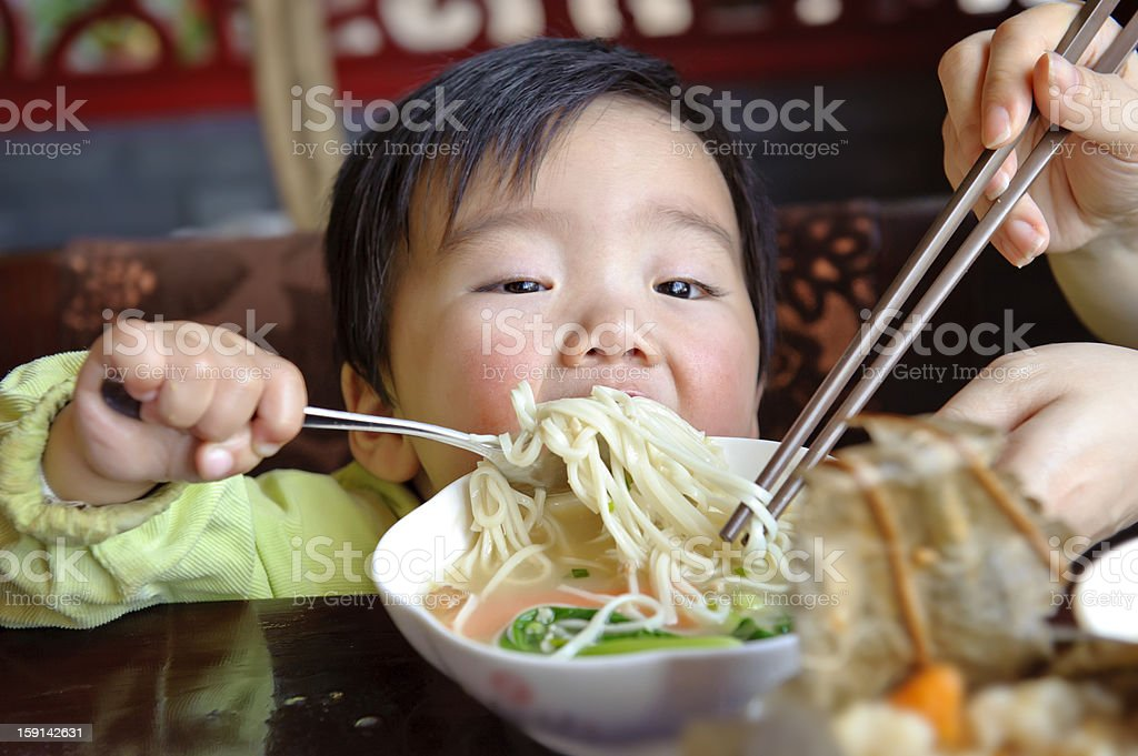 eating baby to grab noodle royalty-free stock photo