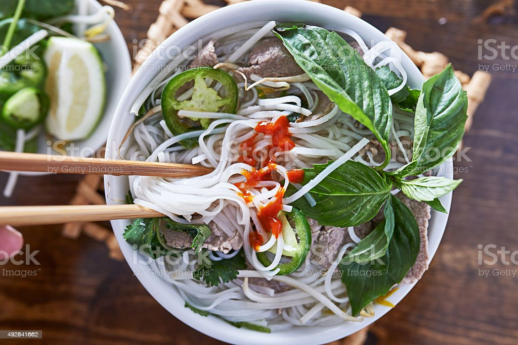 eating beef pho with spicy sriracha sauce shot top down stock photo