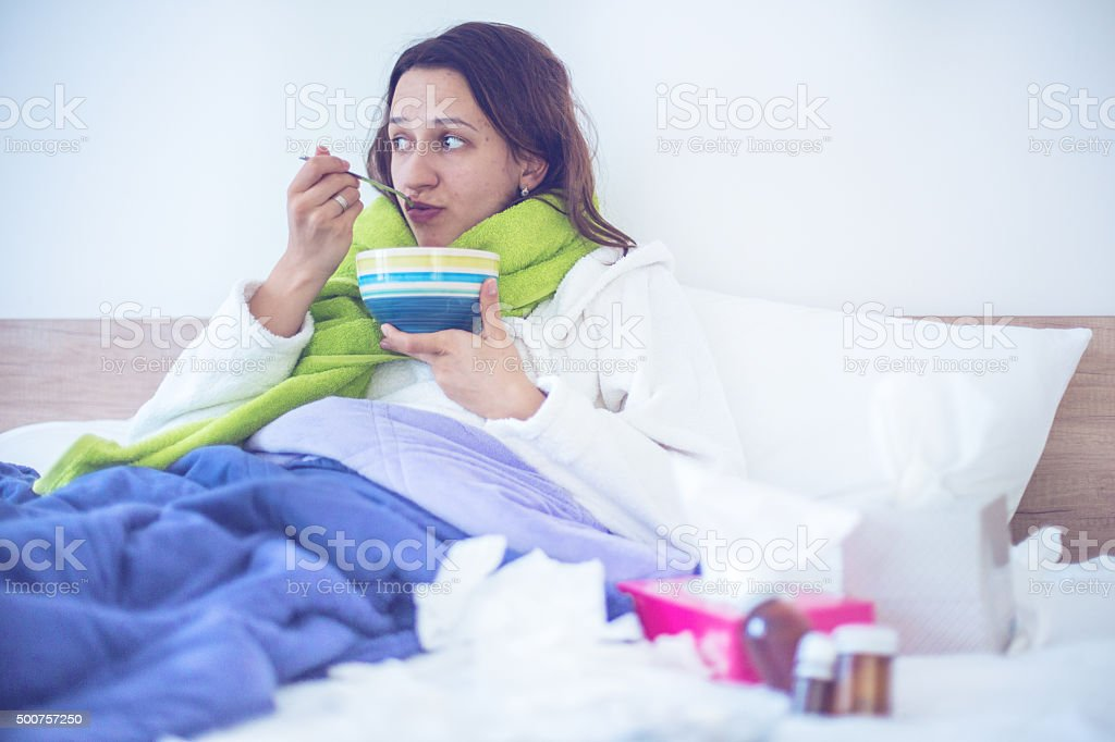 Eating chicken noodle soup in bed while sick stock photo