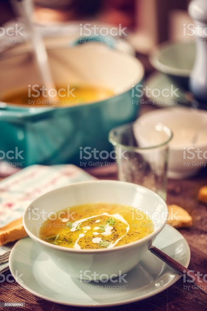 Eating Chicken Soup with Carrots and Parsnips stock photo