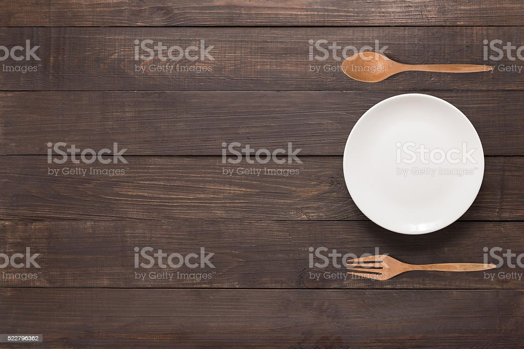 Eating concept. Spoon, fork and white dish on the wooden stock photo