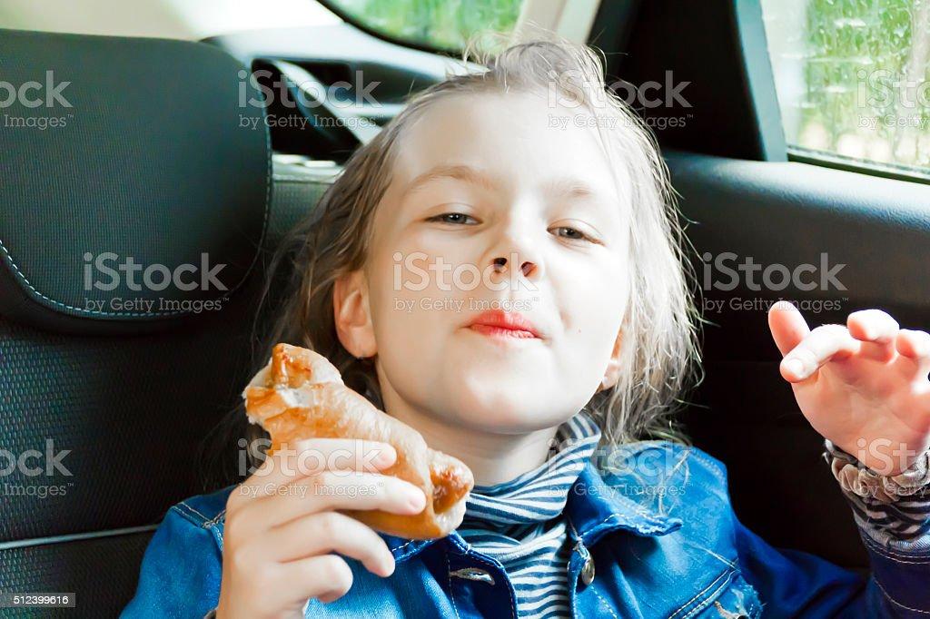 Eating cute girl sitting inside car stock photo