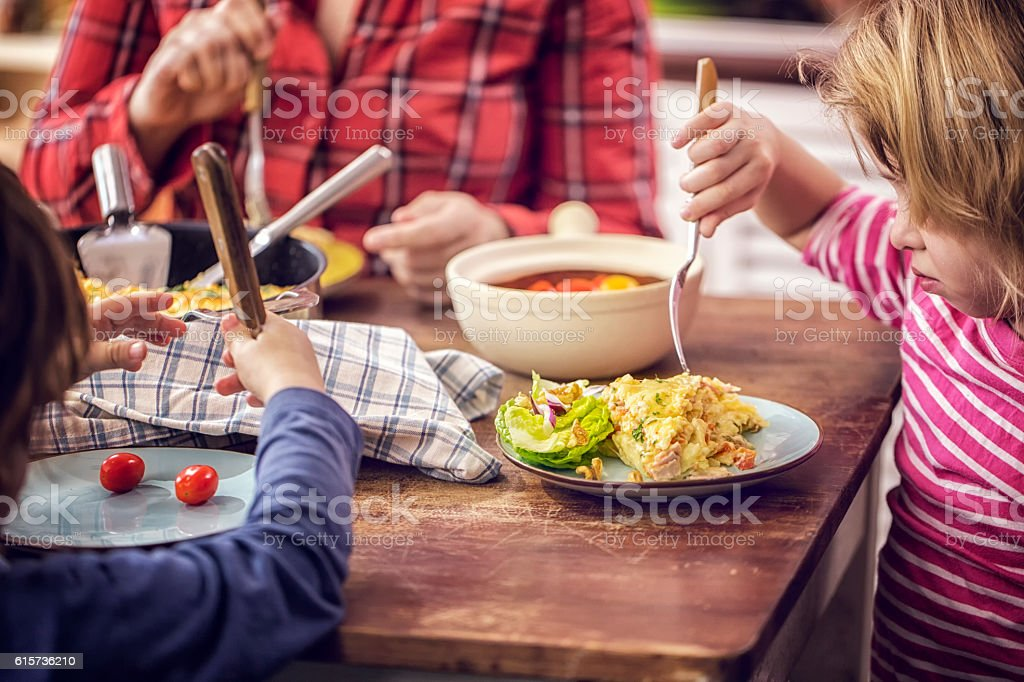 Eating Delicious Baked Crepes Pancakes with Ham and Tomatoes stock photo