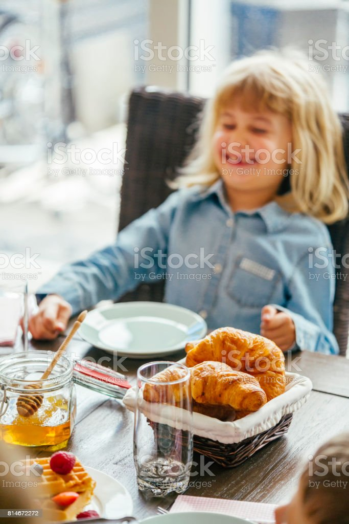 Eating Delicious Breakfast with Coffee, Waffles, Croissants and Fresh Fruits stock photo