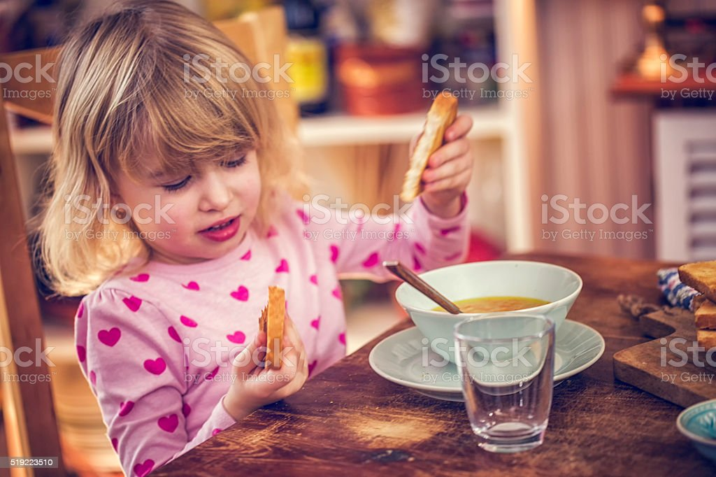 Eating Delicous Chicken Soup with Carrots and Parsnips stock photo