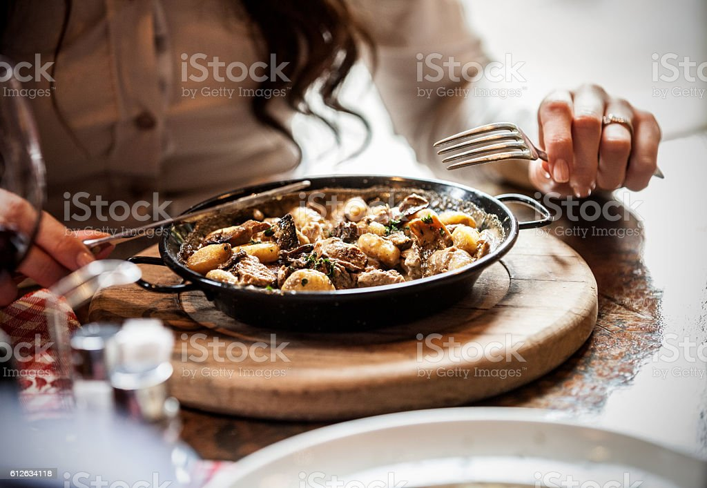 Eating gnocchi with meat stock photo