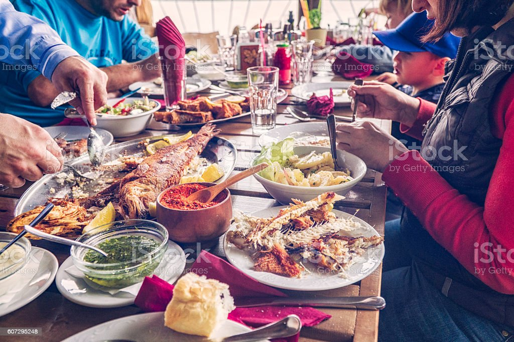 Eating Grilled Fish and Fresh Salad in a Restaurant stock photo