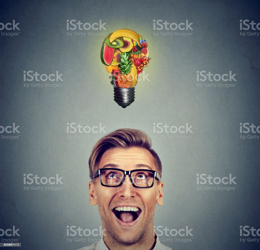 Eating healthy. Man looking up at fruit light bulb stock photo
