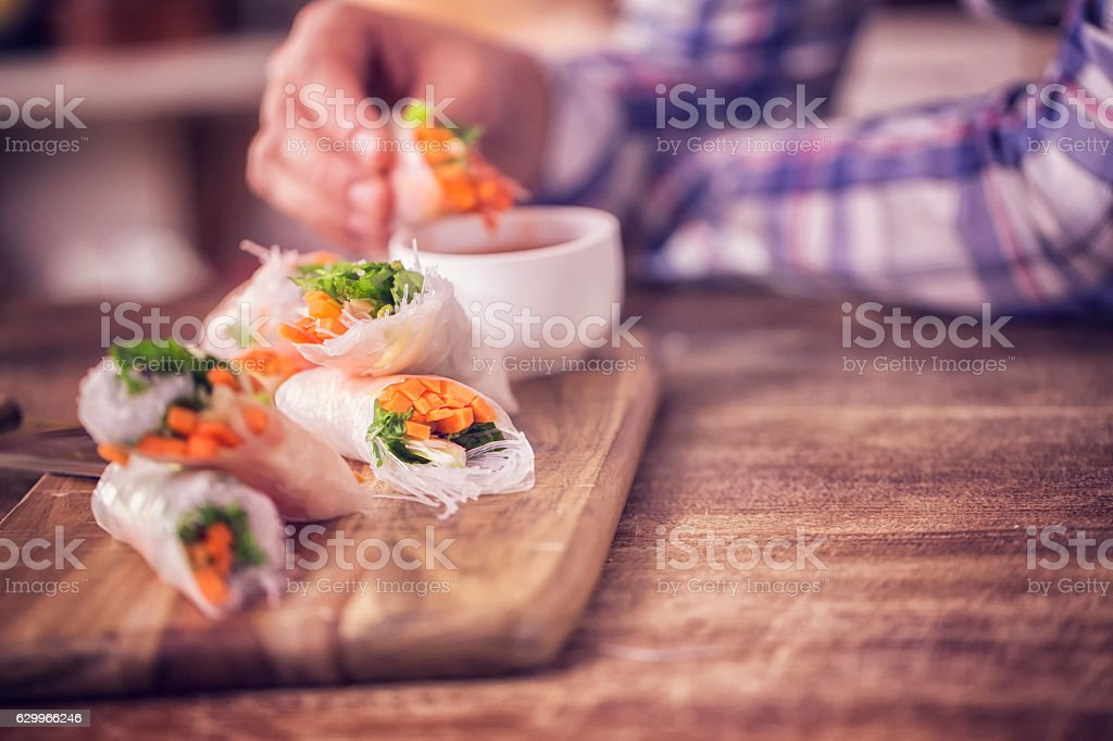 Eating Homemade Spring Rolls with Fresh Vegetables stock photo
