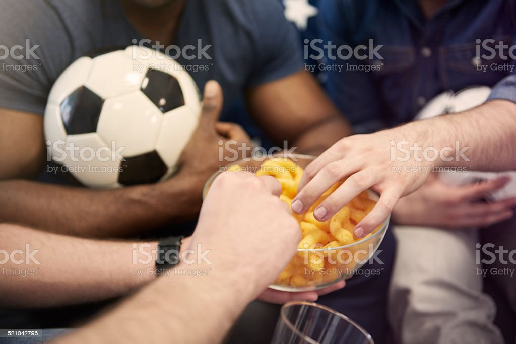 Eating little snack during football match stock photo