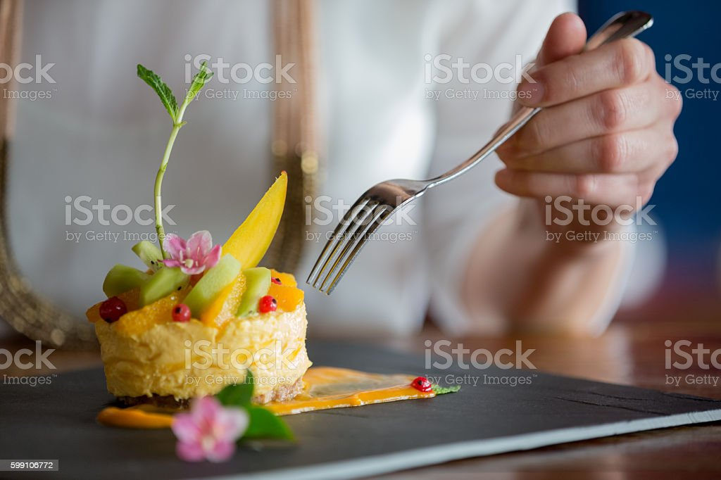 Eating mango mouse cake stock photo