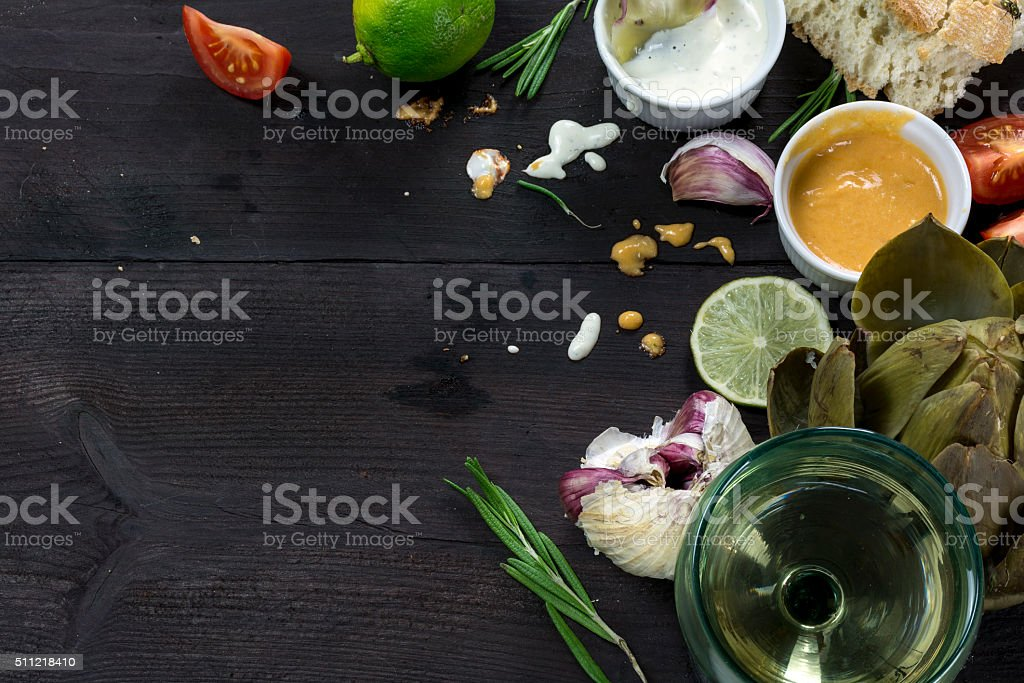 Eating Mediterranean, artichoke with dips, garlic, lemon and bread stock photo